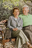 Seniors on a bench. Seniors couple sitting on a bench with a cat in the park Royalty Free Stock Photography