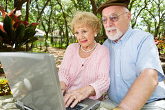 Seniors Browsing the Internet. Senior couple with laptop browses the internet in a beautiful outdoor setting Stock Image