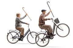Seniors with canes riding bicycles with one of them doing a whee Royalty Free Stock Photography