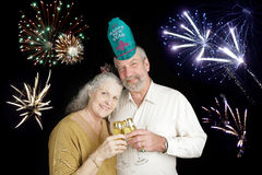 Seniors Celebrate New Years. Beautiful senior couple celebrating a Happy New Year with a champagne toast, while fireworks go off in the background Stock Photos