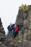 Seniors and child hiking on the rock. Three seniors with child boy pointing and hiking on rocky terrain stock images