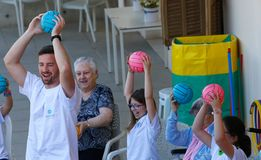 Seniors and childs during therapeutical activities on a nursing home in Mallorca. Seniors with childs and their Medical assistant practice some coordination stock image