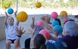 Seniors and childs during therapeutical activities on a nursing home in Mallorca. Seniors with childs and their Medical assistant practice some coordination royalty free stock image