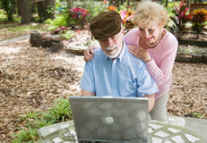 Seniors on Computer with Copyspace. Senior couple on the computer outdoors in a natural setting.  Horizontal view with room for text Stock Images