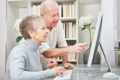 Seniors with computer learn about internet. Together online Stock Image