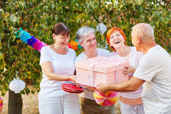 Seniors congratulate their friend with a gift Royalty Free Stock Photo
