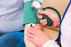 Seniors controlling blood pressure at home. Woman controlling blood pressure with stethoscope and sleeve on arm of man Royalty Free Stock Photo