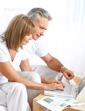 Seniors couple. Working with laptop at home Royalty Free Stock Photos
