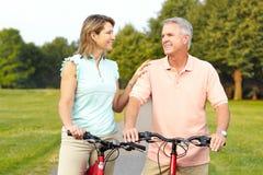 Seniors couple biking. Happy elderly seniors couple biking in park royalty free stock photo