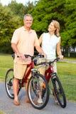 Seniors couple biking. Happy elderly seniors couple biking in park Stock Image