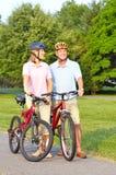 Seniors couple biking. Happy elderly seniors couple biking in park Royalty Free Stock Photos