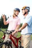 Seniors couple biking. Happy elderly seniors couple biking in park Stock Photos