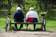 Seniors couple cyclists resting. In forest Stock Images