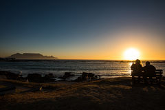 Seniors couple enjoying colorful sunset on the beach at Bloubergstrand in South Africa, facing Table Mountain. Stock Photos