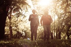 Seniors couple exercising together in meadow. Sunny spring day in nature Stock Image