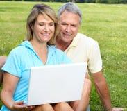 Seniors couple with laptop. Happy elderly seniors couple with laptop in park royalty free stock photo