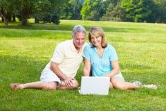 Seniors couple with laptop. Happy elderly seniors couple with laptop in park royalty free stock image