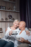Seniors couple sitting in chair, embrace and drink coffee; Stock Photos