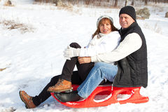 Seniors couple on sled in winter park Stock Image
