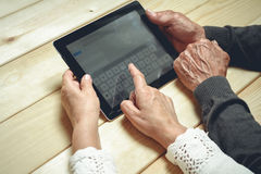 Seniors couple with tablet. Seniors couple sitting at a wooden table with a tablet in hands.  Online education retirement concept. e-Learning Royalty Free Stock Photography