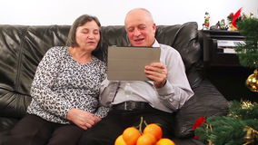 Seniors couple using tablet computer talking with video chat stock video