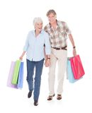 Seniors couple walking with shopping bag Royalty Free Stock Photos