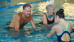 Seniors cycling on aqua bike. Happy smiling mature man and old woman cycling on a swimming bike in swimming pool. Happy and healthy senior people enjoying