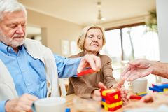 Seniors with dementia stack building blocks. Seniors with dementia or Alzheimer`s in a retirement home stack colorful building blocks together royalty free stock photography