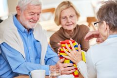 Seniors with dementia play with building blocks. And build a tower in the nursing home stock images