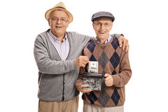 Seniors destroying a dollar in a paper shredder Royalty Free Stock Photography