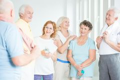 Seniors discussing workout routine. Group of friendly seniors discussing their fun workout routine at the gym royalty free stock photos