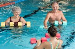 Seniors doing aqua aerobics. Senior couple in training session of aqua aerobics using dumbbells in swimming pool. Mature men and old women practicing aqua Royalty Free Stock Photography