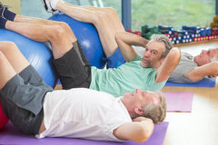 Seniors doing sit-ups at the gym Stock Images