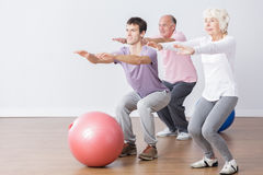 Seniors doing squats. During classes with physiotherapist Royalty Free Stock Photos