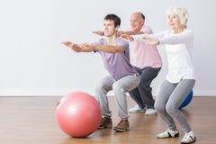 Seniors doing squats Royalty Free Stock Photos