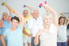 Seniors doing strength building exercises. Seniors doing strength building fitness exercises with dumbbells, holding their left hand over their heads stock photography