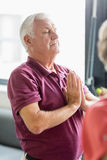 Seniors doing yoga with closed eyes. In a retirement home stock photo