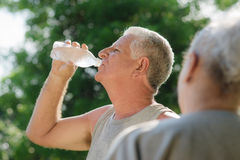 Seniors drinking water after fitness in park. Senior people, old men and women talking and drinking water after exercising in park Stock Photography