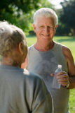 Seniors drinking water after fitness in park. Senior people, old men and women talking and drinking water after exercising in park Stock Images