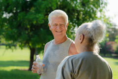 Seniors drinking water after fitness in park. Senior people, old men and women talking and drinking water after exercising in park Royalty Free Stock Images
