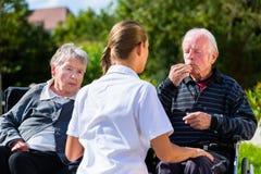 Seniors eating candy in garden of nursing home Stock Image
