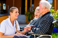 Seniors eating candy in garden of nursing home Royalty Free Stock Image