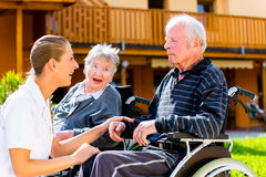 Seniors eating candy in garden of nursing home Royalty Free Stock Photography