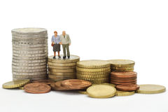 Seniors with euro coins. Seniors figurines with euro coins isolated on white background Royalty Free Stock Photos