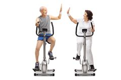 Seniors on exercise bikes high-fiving each other. Isolated on white background Royalty Free Stock Photography