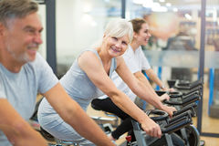 Seniors on exercise bikes in spinning class at gym stock images