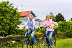 Seniors exercising with bicycle Stock Images