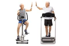 Seniors exercising on a stationary bike and a treadmill high-fiv. Ing each other isolated on white background Royalty Free Stock Photos