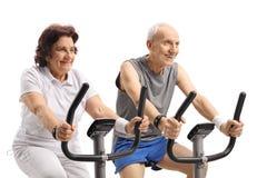 Seniors exercising on stationary bikes stock photography
