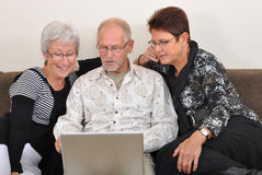 Seniors exploring the web. Seniors man and women exploring the web Stock Photo
